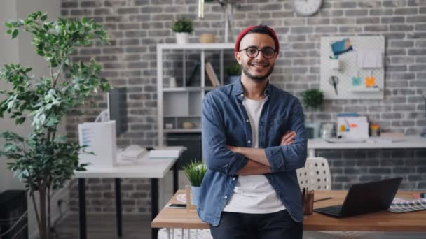 Portrait of cheerful guy entrepreneur standing in creative office and smiling