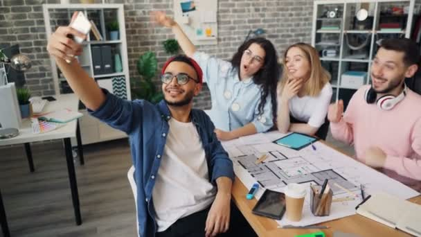 Company employees taking selfie in creative office using smartphone camera