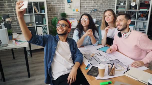 Business owner taking selfie with creative team with smartphone camera in office
