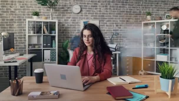 Zoom in time-lapse of young woman using laptop working at project in office