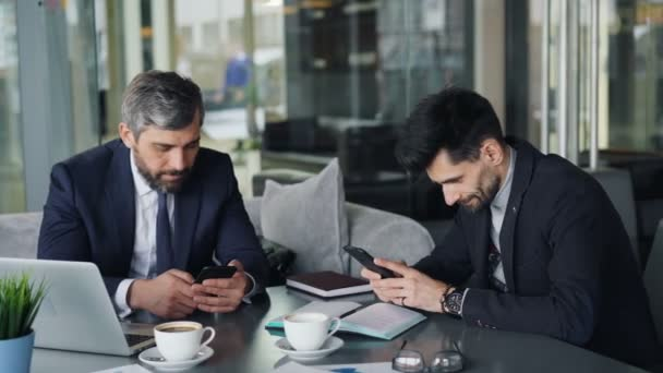 Male colleagues using smartphones touching screen meeting in cafe for coffee