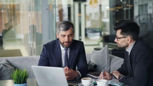 Érett üzletemberek beszél kávézóban nézi laptop képernyőn megvitatása szerződés