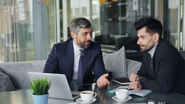Mature men business partners negotiating deal talking using laptop in cafe