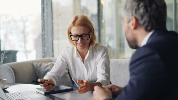 Business partners cheerful man and woman talking in cafe looking at papers