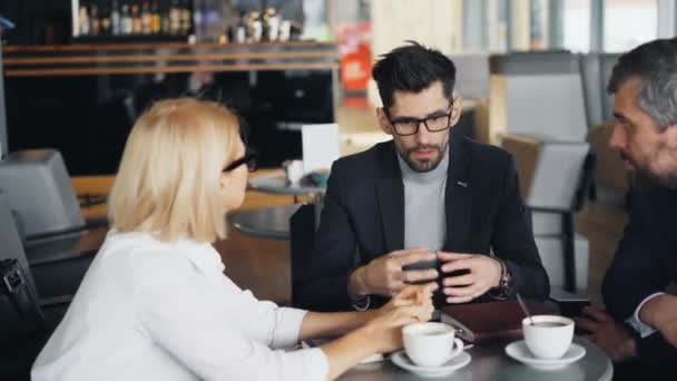 Bearded businessman speaking with male and female partners in modern cafe