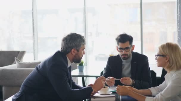 Business team middle aged men and senior woman talking in cafe over coffee