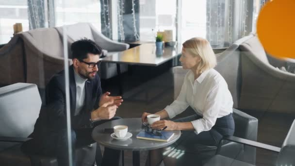 Business partners man and woman sharing news talking in cafe over coffee