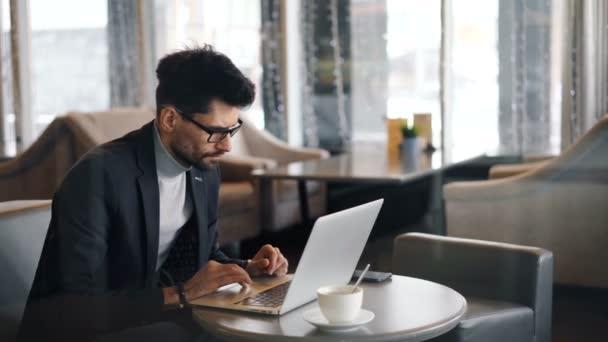 Podnikový manažer pracující v kavárně při polední přestávce s využitím moderního notebooku