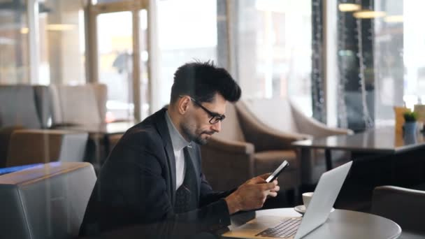 Confident bearded man in glasses using smartphone during coffee break in cafe