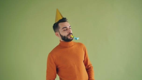 Hravý mladý muž s narozeninovým kloboukem, který se baví na večírku