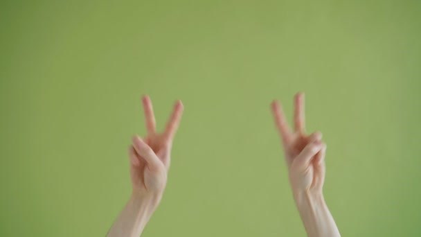 Close-up shot of human hands making v-sign moving dancing on green background