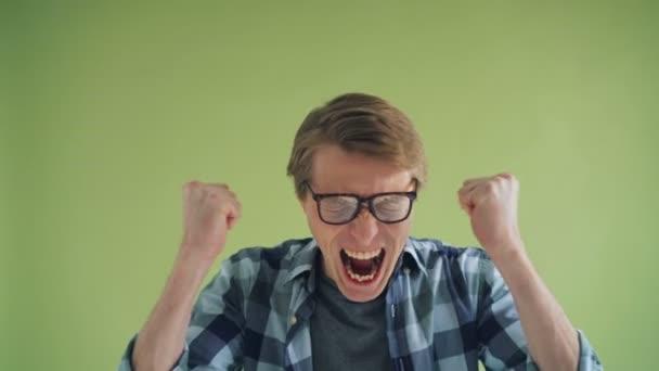 Porträt eines schreienden jungen Mannes verrückter Hipster schreit auf grünem Hintergrund