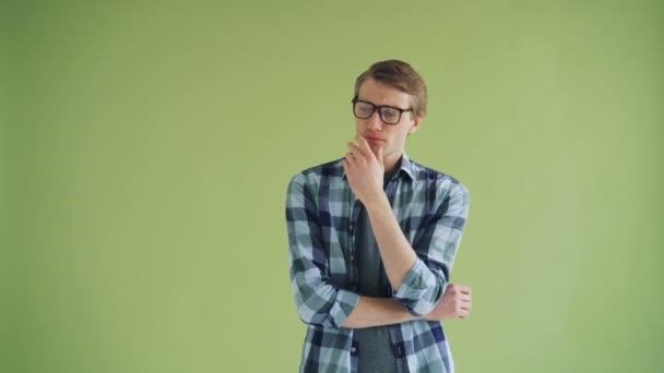 Portré gondolkodó ember szemüveg nézi kamera zöld háttér