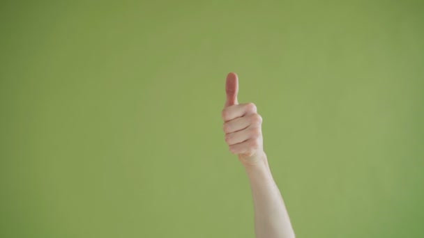 Close-up shot of male hand changing thumbs-up into thumbs-down on background