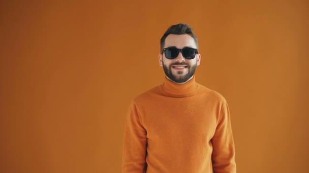 Portré divatos srác figyelemfelkeltő napszemüveg és mosolyogva nézi kamera egyedül