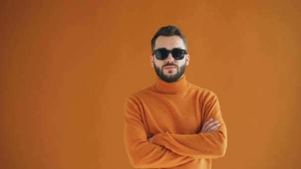 Portrait of confident bearded guy in sunglasses standing with asrms crossed