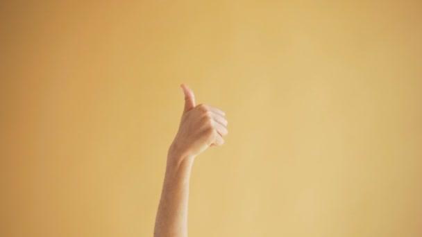 Blízka ženských rukou ukazující na oranžové pozadí gesto palce nahoru