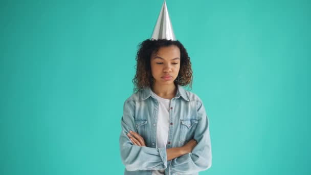 Portrait of unhappy mixed race girl in party hat standing with arms crossed