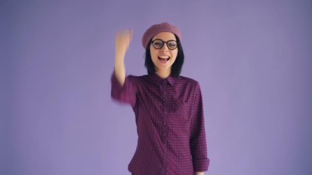 Portrait of lucky young lady raising fist enjoying success and good luck