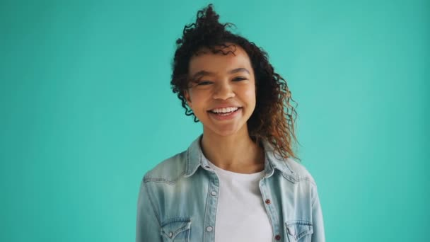Slow motion of pretty African-American girl with curly hair fluttering in wind