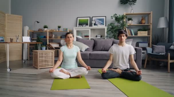 Girl and guy young people meditating in lotus position in apartment