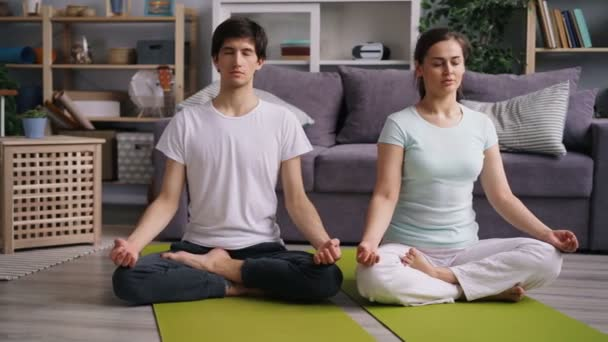 Young people girl and guy relaxing in lotus pose with closed eyes after yoga