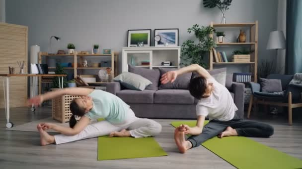 Young family husband and wife doing yoga then relaxing in lotus position