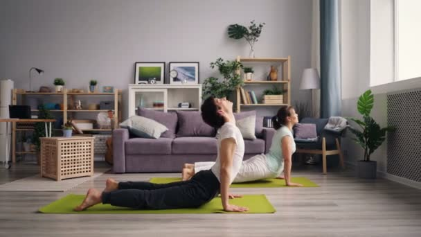 Young family man and woman practising dog positions during yoga practice at home
