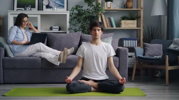 Dívka, která mluví na mobilním telefonu a používá přenosný počítač, když přítel medituje na rohoži jóby