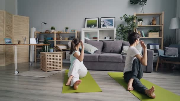 Couple girl and guy practising yoga in apartment sitting on floor twisting body