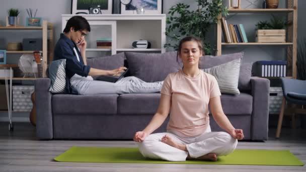 Mladá dáma medituje v lotosové pozici, zatímco chlap mluví po telefonu přes laptop