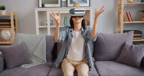 Young lady enjoying new experience in augmented reality glasses sitting on sofa