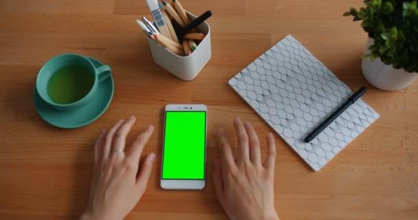 Nő mozgó kezek ujjak-ra asztal mellett Smartphone-val zöld modell-megjelöl képernyő
