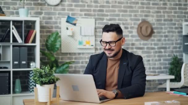 Portrét atraktivního podnikatele, který používá přenosný počítač a pak se dívá na usměvavý fotoaparát