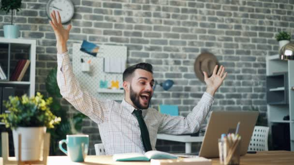 Seamless loop of happy businessman smiling with raised arms looking at laptop