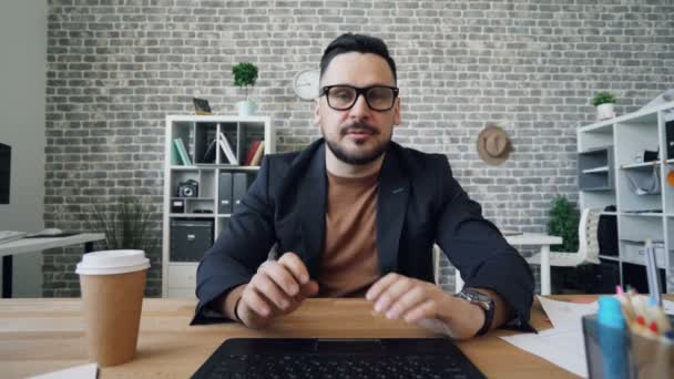 Bearded man talking online using computer looking at camera gesturing in office