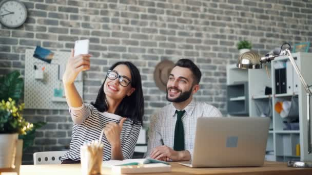 Man and woman colleagues taking selfie with smartphone camera in office