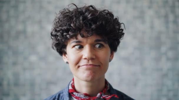 Blízký portrét hloupé mladé ženy, jak se jí lesknou oči a směje se