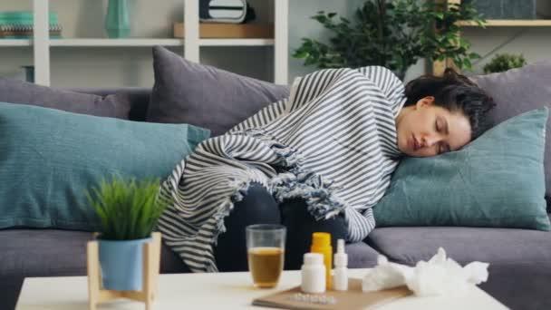 Kranke junge Frau schläft bei Krankheit entspannt auf Couch in Wohnung