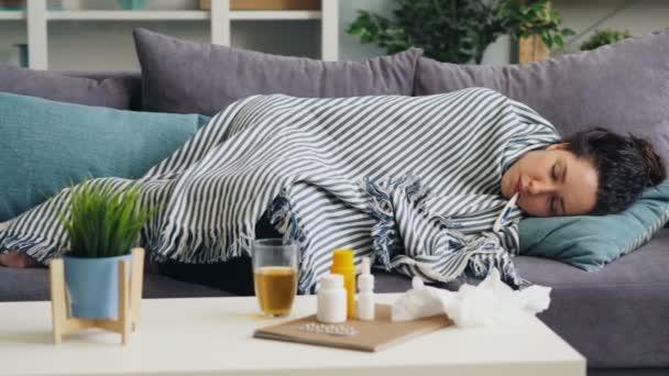 Kranker Student schläft mit Thermometer im Mund auf Couch unter Decke liegend