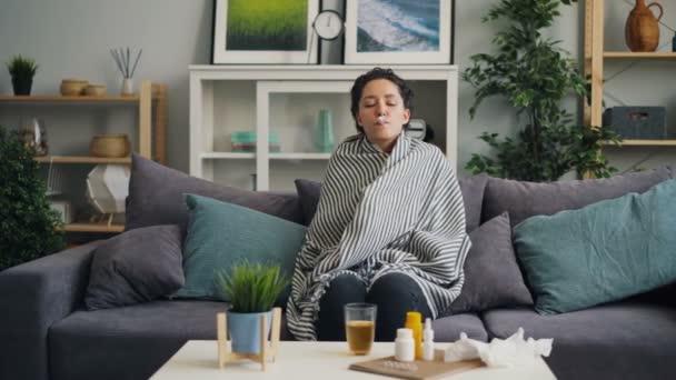 Kranke Studentin nimmt Temperatur und trinkt Medizin zu Hause
