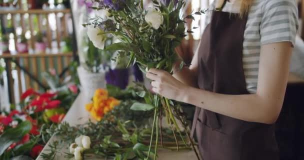 Dívka v zástěře, která se složením krásných barevných květin drží