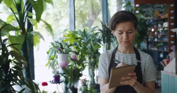 Cute business owner writing down information working in flower shop alone