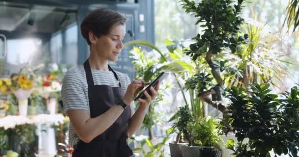 Mladý podnikatel, který se dotýká obrazovky tablet a dívá se na květiny ve květinářství