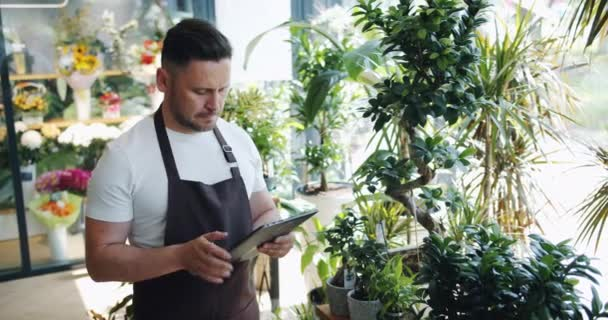 Slow motion of man flower store owner using tablet at work touching screen
