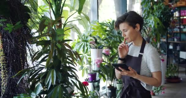 Young entrepreneur counting flowers in floral shop and using tablet at work