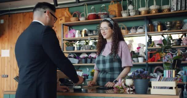 Šťastný zákazník nakupující hromadu květin za bankovní kartu v květinářství