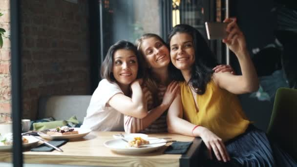 Group of friends girls taking selfie in cafe holding smartphone sitting at table