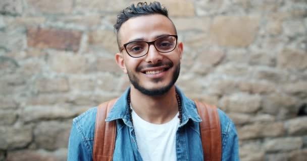 Portré vonzó fiatal Arab mosolygós nézett kamera közelében téglafal