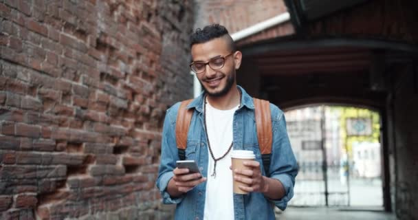 Smiling Middle Eastern guy using smartphone outdoors and holding to go coffee